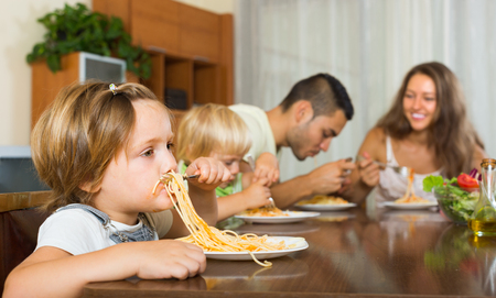 italienisches essen: Happy smiling family with playful kids eating with spaghetti at table. Focus on girl
