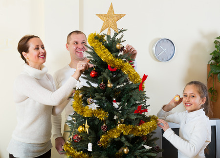9 10 years: Happy parents and their child preparing for Christmas at the living room