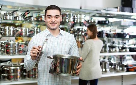 utensilios de cocina: Sonriente pareja en la secci�n de utensilios de cocina en el hipermercado Foto de archivo