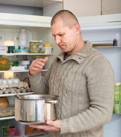 frowy: Man holding nose because of bad smell near fridge at home