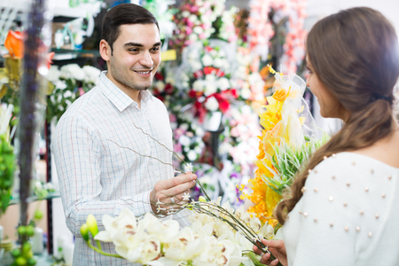 flower seller: Woman seller 20s helping to pick floral bouquet of flowers man at flower shop Stock Photo