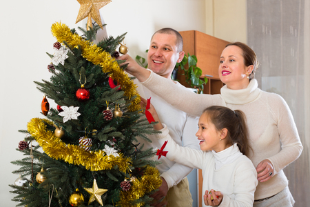 7 8 years: Happy smiling parents and daughter decorating Christmas tree in the living room at home