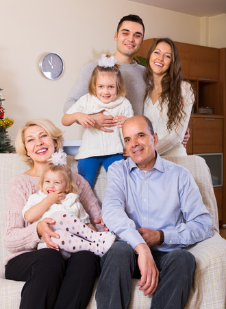 60 65: Portrait of happy big multigenerational family in the living room at home