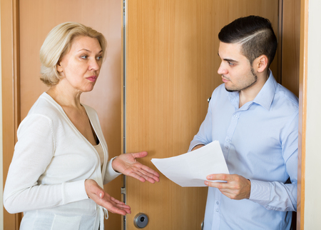 Businessman trying to collect arrearages from mature blonde woman at home door