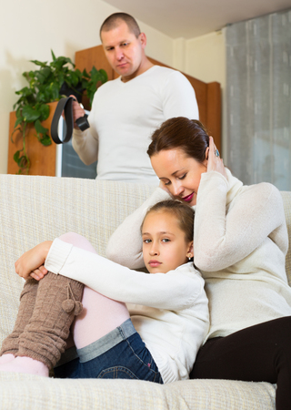home comforts: Sad mother comforting litlle daughter at home and angry father