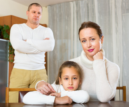 home comforts: Family of three with sad woman, daughter and angry man having conflict Stock Photo