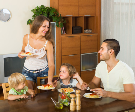 3 4 years: Smiling young family of four eating spaghetti at home interior