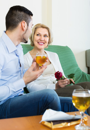 mismatch: Happy blonde mature woman chatting with young boyfriend indoors Stock Photo