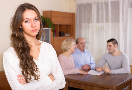 staying: Sad girl staying against united family members Stock Photo