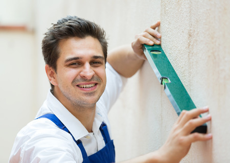 smoothing: Smiling constructor smoothing the wall surface indoors