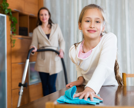 30 35: Woman with vacuum cleaner and smiling daughter with rag in home