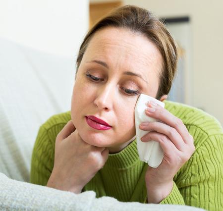 mujer triste: mujer morena solitario infeliz llorando en el sofá en casa Foto de archivo