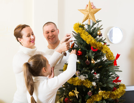 Happy family with daughter decorating Christmas tree in the living room at home. Focus on woman