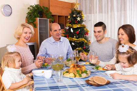 30 35: Mature parents with adult kids and grandchildren celebrating New Year today