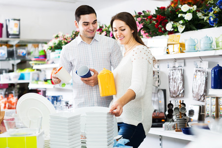 bonny: Smiling couple buying ceramic tableware in shop cookware