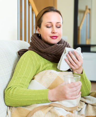 linctus: Ill woman sitting on a couch at home. She holds a folded towel in one of her hands and a glass of warm medicine in another Stock Photo