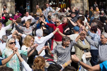 BARCELONA, SPAIN - APRIL 5, 2015: Mature people dancing circle dance long sardana at Ballades al Pla de la Catedral holiday.