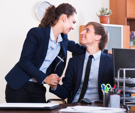 co action: Playful flirting between team managers at work in office Stock Photo