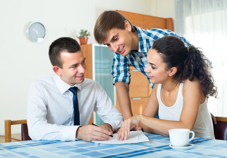 25 35: Banking agent offering young couple good mortgage deal indoors