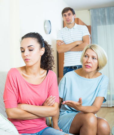 daughter in law: Adult girl having quarrel with husband and mother-in-law Stock Photo