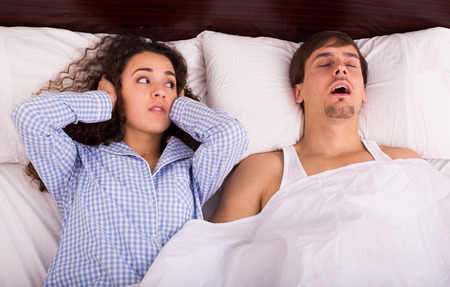 Angry brunette wife disturbed with husband loud snoring Reklamní fotografie