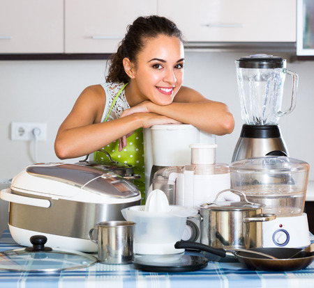 Retrato de la muchacha sonriente morena con aparatos de cocina en el hogar
