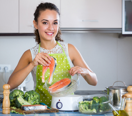 jorobado: Smiling young housewife steaming salmon and vegetables in domestic kitchen