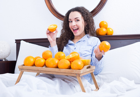 25 35: Portrait of brunette with sweet oranges and juice in tray Stock Photo