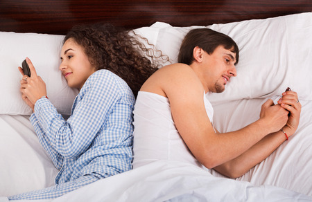 mid distance: Boyfriend and smiling young girlfriend busy with smartphones in domestic bedroom Stock Photo
