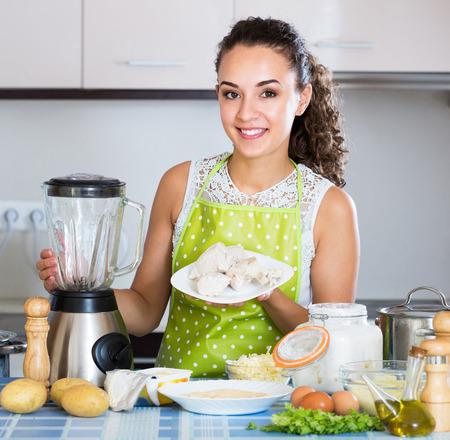 25s: Cheerful housewife grinding paste ingredients in blender indoors