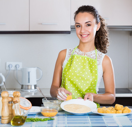 crocchette: Smiling girl preparing croquettes for tasty dinner at home Stock Photo