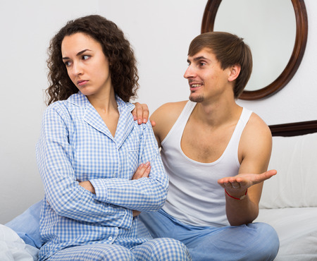 impotent: Smiling man comforting offended wife in bedroom after quarrel