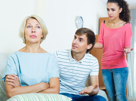 mother in law: Frustrated woman watching how adults trying to reconcile with her Stock Photo