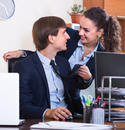 co action: Sexual harassment in office: smiling female director flirting with employee Stock Photo