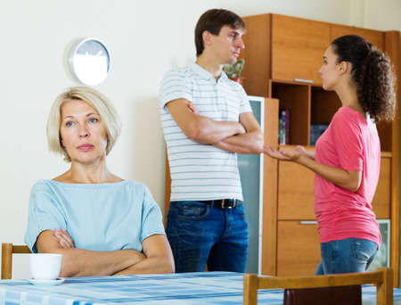 daughter in law: Husband and wife quarrelling indoors, senior mother taking it hard Stock Photo