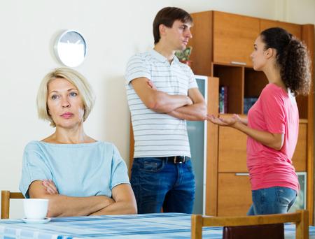 25 35: Husband and wife quarrelling indoors, senior mother taking it hard Stock Photo