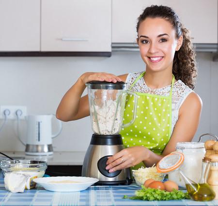 liquidiser: Happy young girl preparing chicken pate in domestic kitchen