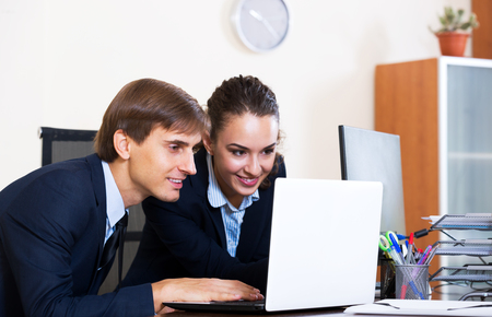 yuppie: White-collar work: two cheerful managers employees in modern office. Focus on the man
