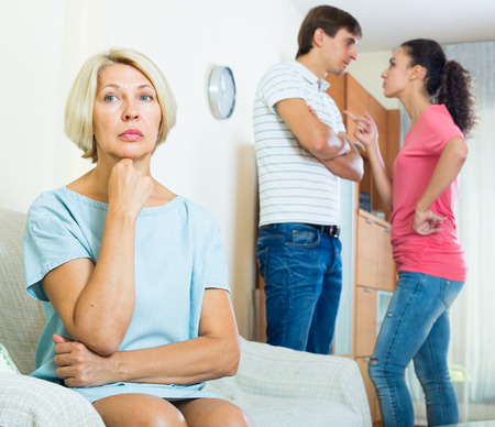 Husband and wife quarrelling indoors, senior mother taking it hard Stock Photo