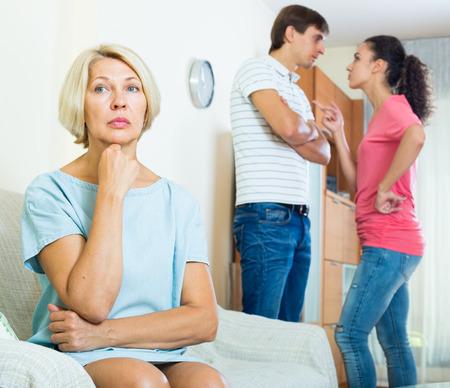 Man en vrouw ruzie binnenshuis, senior moeder die het moeilijk Stockfoto