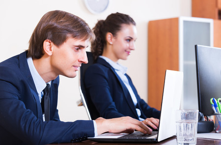 yuppie: Positive young office colleagues successfully working together indoors Stock Photo