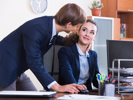 tempter: Sexual harassment in office: manager caressing employee and smiling