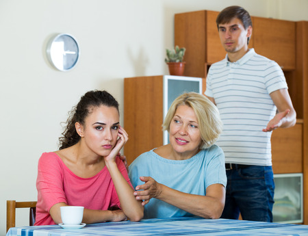 mother in law: Mature woman helping offended daughter to reconcile with husband Stock Photo