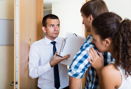 broken contract: Debts collector and family couple standing in doorway of flat