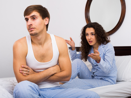 impotent: Stressed man sitting apart in bed during quarrel with wife Stock Photo