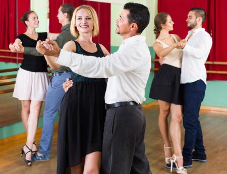 tango: Smiling young adults having tango class at dance studio. Selective focus