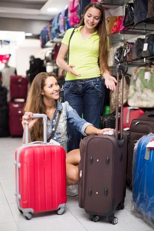 portmanteau: adult russian woman choosing luggage bag in shop Stock Photo