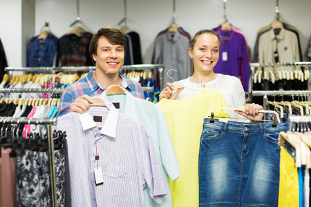 choosing clothes: Smiling couple choosing clothes in the shop. Focus on man Stock Photo