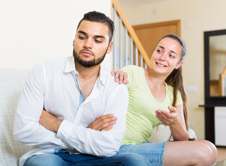 spat: Unhappy wife listening smiling husband Stock Photo