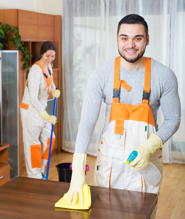 houseman: Happy professional cleaners with equipment clean in living room of client house Stock Photo